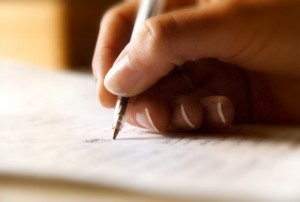 Image of a content writer's hand holding a pen